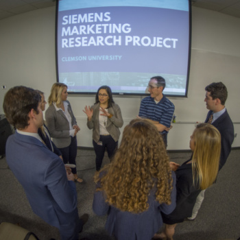 "A high view looking down on a group of Clemson students and two Siemens employees talking in a circle, with a video screen behind them with the words ""Siemens Marketing Research Project"" on it."