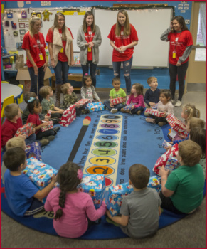 Five ladies in red shirts look down on a circle of kindergartners sitting on a blue carpet, each holding a present in their lap.