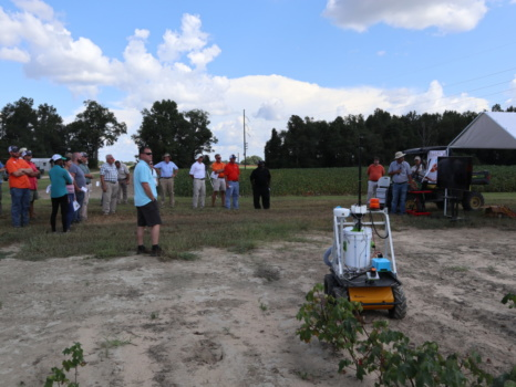 Participants at the 2018 Edisto Research and Education Field Day listen with interest at researcher Joe Mari Maja talks about a UGV cotton harvester he is working to develop.