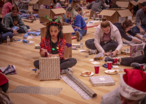 A girl wearing a red shirt and reindeer antlers on her head wraps a present on a gym floor surrounded by other people wrapping presents.