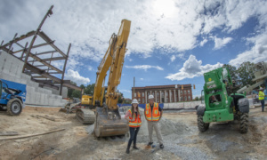 Erin Carpenter and Paul Borick stand in front of large construction equipment with Sirrine Hall and the frame of the new College of Business facility in the background.