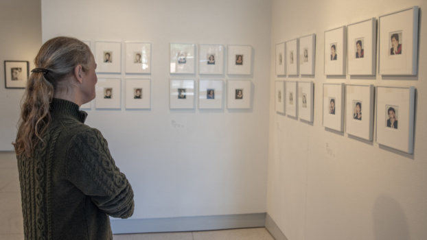 A woman in a green sweater looks at a wall of framed Polaroid photographs.