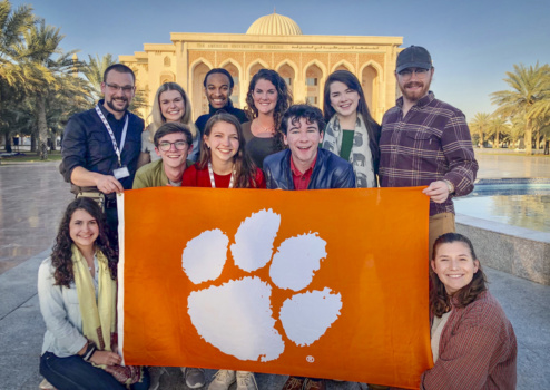 Ten people stand in a group holding a large Clemson Tiger paw flag, with a Middle Eastern-style building and palm trees behind them