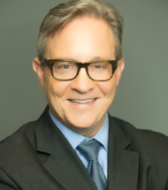 Headshot of Steve Warner, glasses, gray suit against gray background
