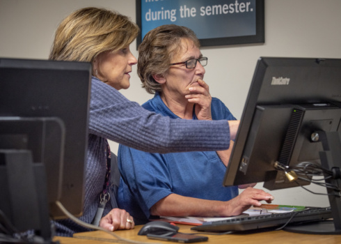 Two women look at a computer monitor with one of them pointing at the monitor and the other with her chin in her hand.