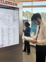 A student navigates the map of prospective employers during a career fair.