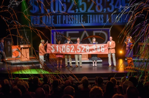 The final campaign number is revealed on stage at an event. The number on the banner reads $1,062,528,346.