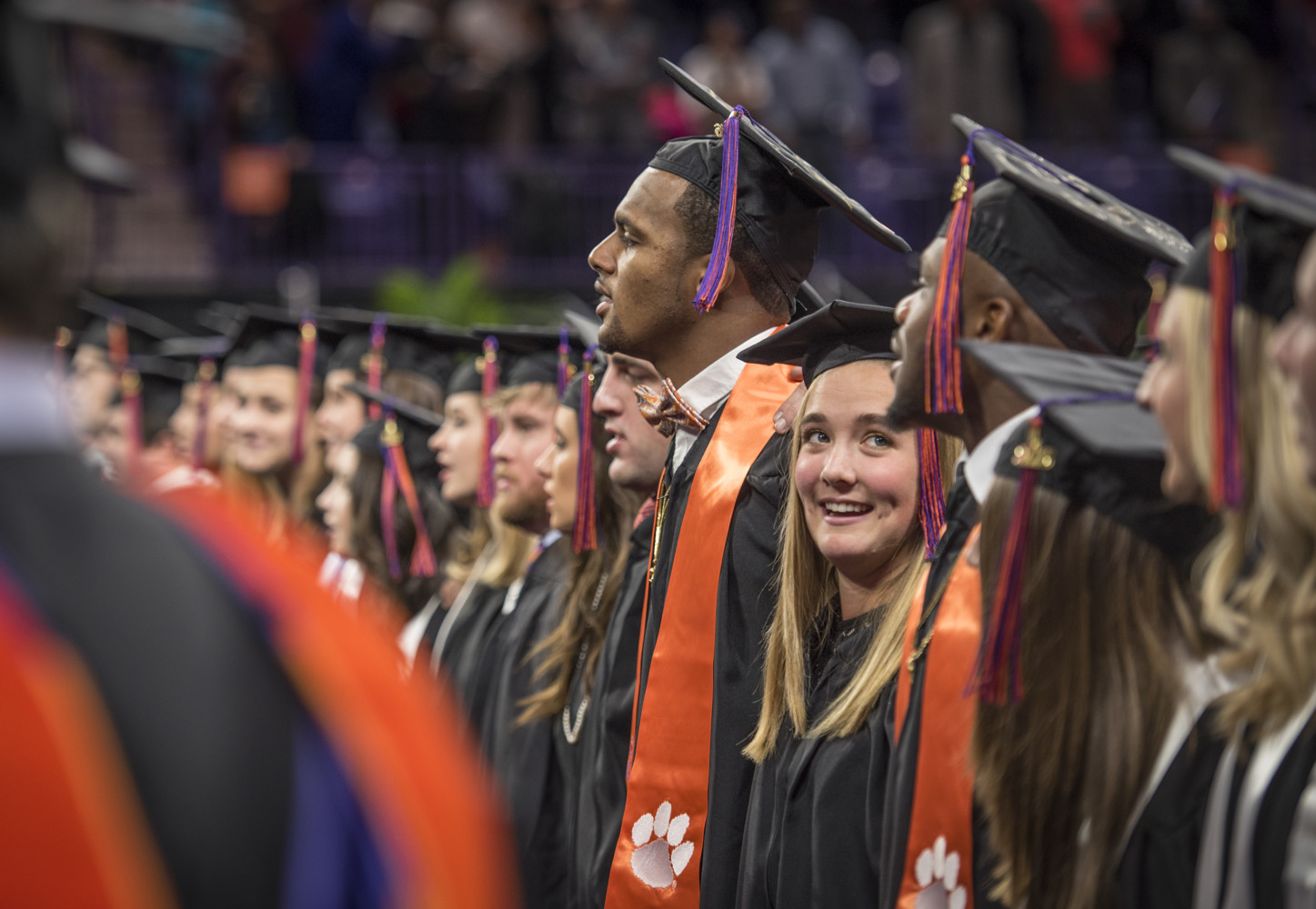 93ec4bb3bf0 A row of graduates in caps and gowns sing the alma mater. Clemson University  ...