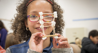 A young girl with glasses looks at the camera through a model building she made out of toothpicks and marshmallows.
