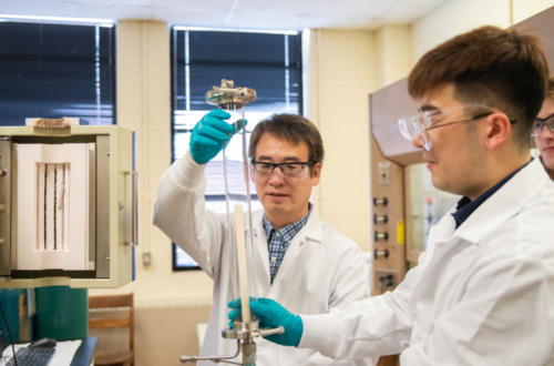 "Jianhua ""Joshua"" Tong, left, and Ph.D. student Shenlong Mu work in their Sirrine Hall lab, where they are working on new technology that combines 3D printing and laser processing."