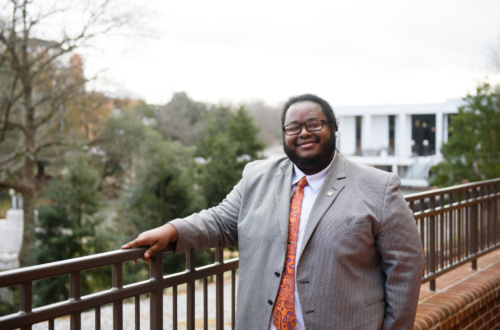 Jerad Green stands with his hand leaning on a metal rail. The Clemson Library is seen in the background.