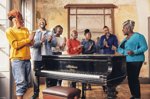 Members of the Kingdom Choir stand in a semi-circle around a piano and sing.