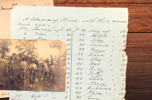 Historic documents and images are spread out on a table.